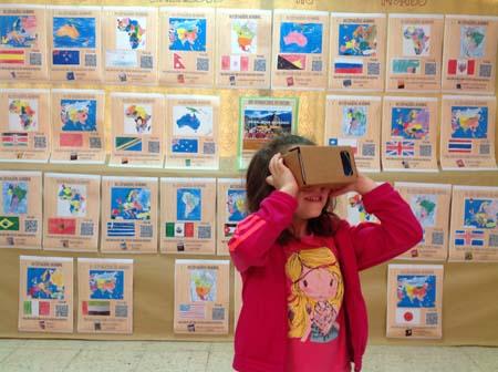 Alumnado de Infantil interactuando con la exposición sobre turismo con realidad aumentada.