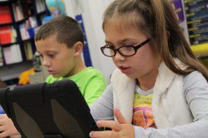 Niño y niña mirando datos en tablet