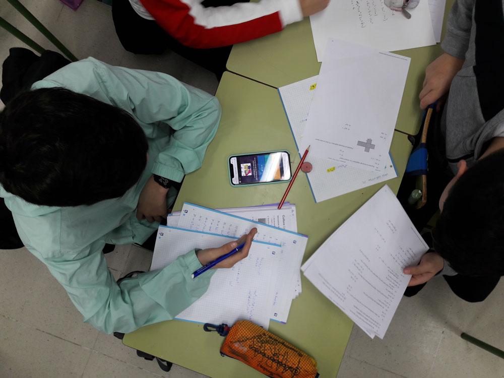 Alumnos resolviendo una prueba de Quizizz a través de sus teléfonos móviles.