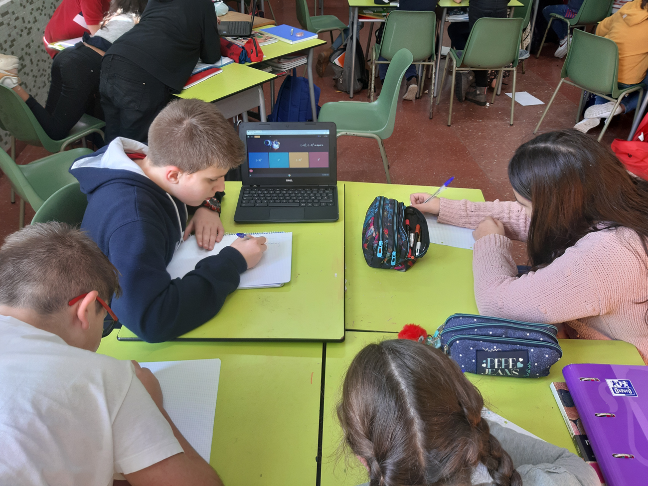Alumnos trabajando con los Chromebooks para superar una prueba de conquista.