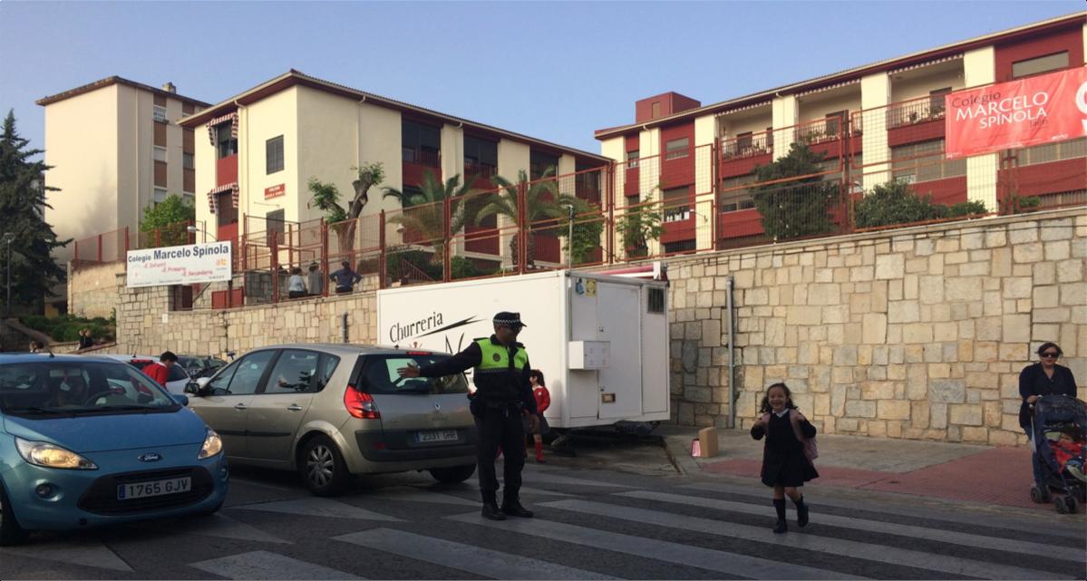 La policía local dando paso a los alumnos a la entrada y salida del colegio.